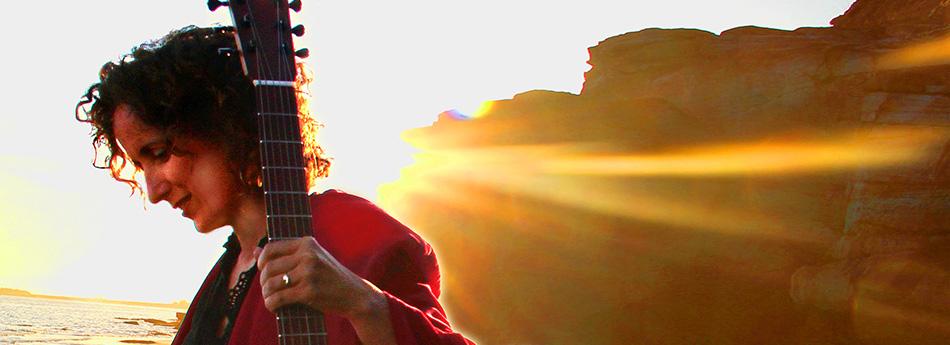Teresa with guitar against setting sun