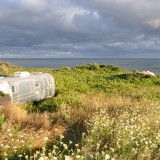 Airstream nestled in the field overlooking the water at Rock Barra