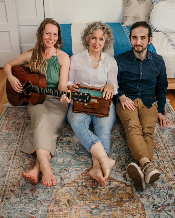 Katlin Doyle, Teresa Doyle and Patrick Bunston seated together with instruments on rug